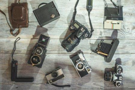 Photo pour Ensemble de caméras vintage et nouvelles sur fond en bois - image libre de droit