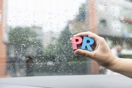 Photo pour Gros plan de la main tenant des lettres en bois PR - image libre de droit