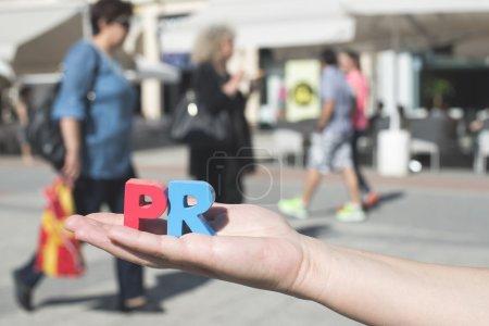 Photo pour Femme tenant des lettres en bois PR. Marcher les gens en arrière-plan - image libre de droit