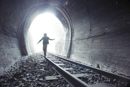 Photo pour Enfant marchant dans le tunnel ferroviaire. Vêtements vintage - image libre de droit