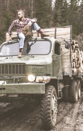 man on vintage truck with logs