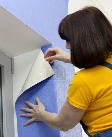 Woman putting up wallpaper...