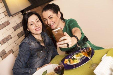 Photo pour Deux femmes utilisant un téléphone intelligent. Au restaurant lors d'un dîner - image libre de droit