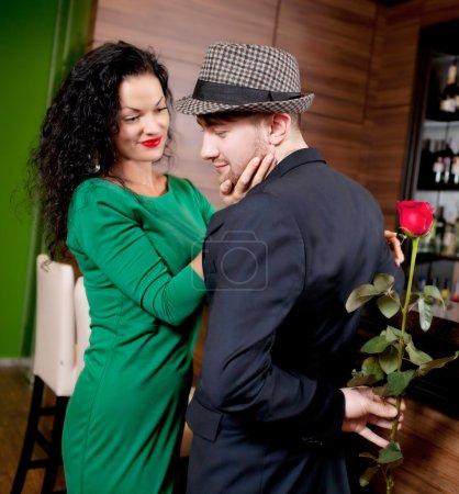 Photo pour Le jeune homme avec une fleur dans une main et la belle fille dans le café - image libre de droit
