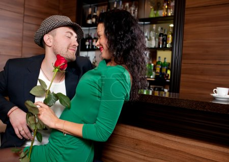 Man with a flower in a hand and the fine girl in cafe
