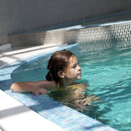 Photo pour Petites filles dans l'eau bleue de la piscine - image libre de droit