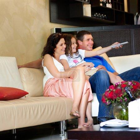 Photo pour Heureux wathching famille jeune plat à l'intérieur de la maison moderne - image libre de droit