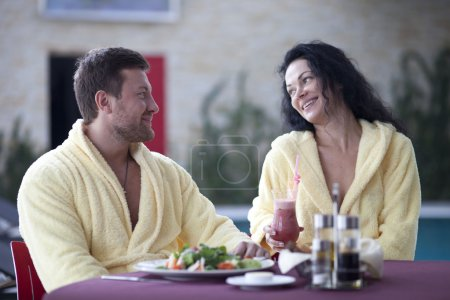 Cute couple in bathrobes having breakfast together at hotel