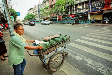 Street trader driven cart with melons at a market