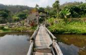 Small wooden bridge over river in old Thai village with trees around