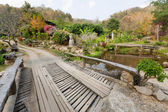 Big wooden bridge over river in old Thai village with trees around