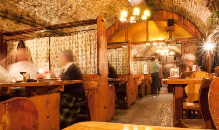 Elderly people meeting for dinner in old fashioned restaurant with brick walls