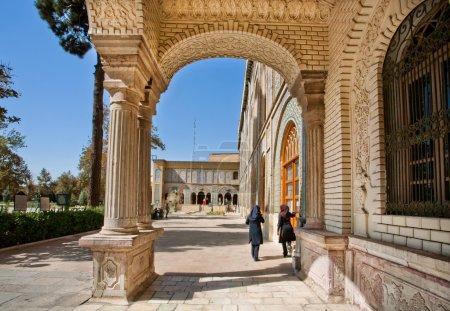 Woman in muslim dress walk through the royal courtyard