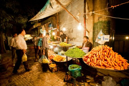 Market traders sell vegetables and fruits on the night bazaar
