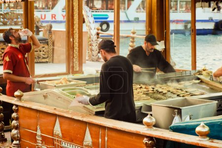 Photo for ISTANBUL, TURKEY - AUG 4: Fast food buffet workers on the boats with popular fish sandwich menu. Bordered on 3 sides by seas, Turkey is a nation of water. - Royalty Free Image