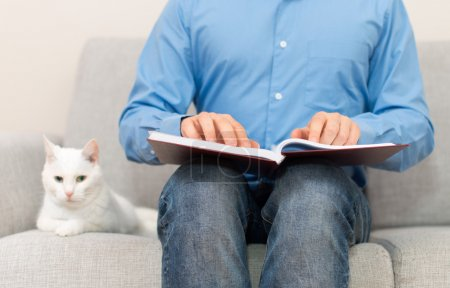 Blind man reading braille book on the couch.