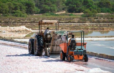 Sea salt production. Salt evaporation pond with tractor.