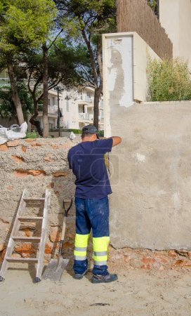 Worker embeds concrete wall outdoors. Renovation works.