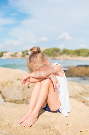 Sad little girl sitting on the beach. Place for text.