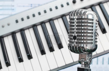 Retro microphone over piano and recording software background.
