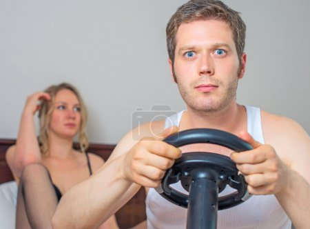 Photo for Video game addiction. Man playing video game with steering wheel, upset woman on background. - Royalty Free Image