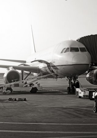 Passenger plane in the airport. Aircraft maintenance. Black and white photo.