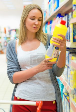 Woman choosing household chemicals in the store.