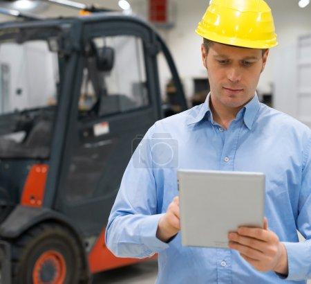 Photo pour Manutentionnaire dans un casque avec tablet pc à l'entrepôt. - image libre de droit