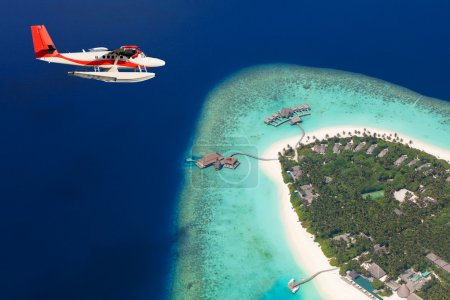 Sea plane flying above Maldives islands