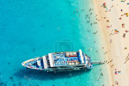 Aerial view of a beach with big boat and people