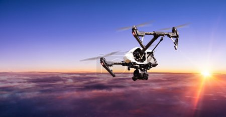 Photo for Drone for industrial works flying above clouds in sunset. Concept of pottential danger of aircraft collision - Royalty Free Image