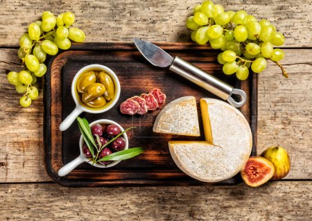 Various kind of cheese and delicacy on wood