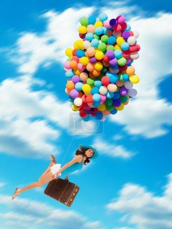 Photo pour Jeune femme tenant des ballons et une vieille valise, volant au-dessus des nuages. Concept de voyage et de liberté - image libre de droit