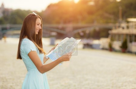 Photo for Female tourist with map visiting city, portrait photography, old town center on background - Royalty Free Image