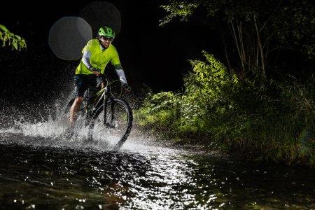 Mountain biker riding in forest stream