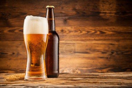Стекло и бутылка пива на деревянных досках