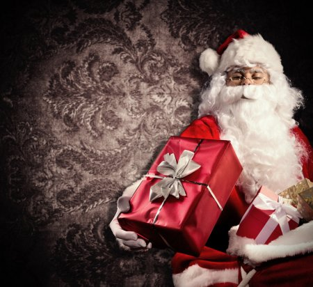 Photo for Christmas concept with Santa Claus in costume holding gifts. Dark pattern as background - Royalty Free Image