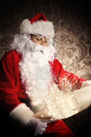 Photo for Christmas concept with Santa Claus in costume holding wish list. Dark pattern as background - Royalty Free Image