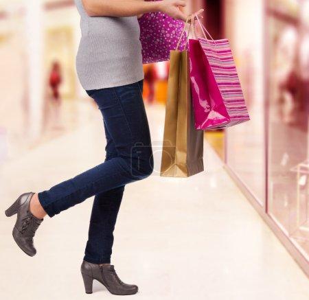 Photo pour Femme dans un centre commercial. Détail des jambes et sacs à provisions . - image libre de droit