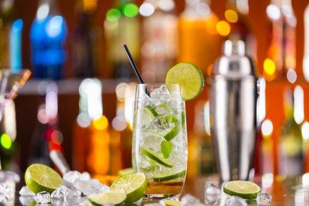 Foto de Copa coctel Mojito en la barra de bar con desenfoque de botellas en el fondo - Imagen libre de derechos