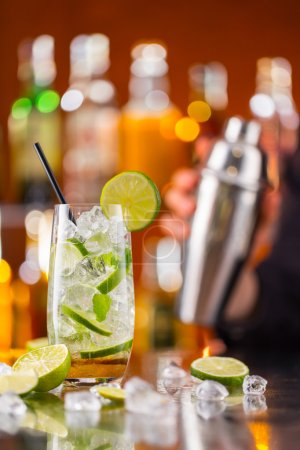 Photo for Mojito cocktail drink on bar counter with barman holding shaker on background - Royalty Free Image