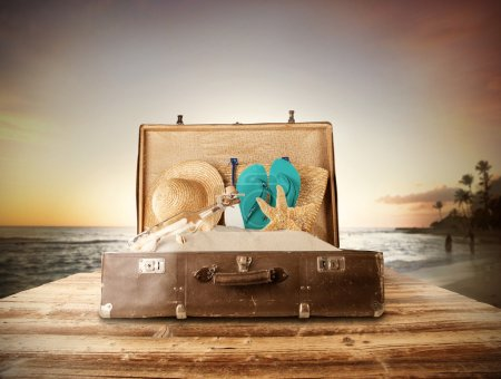 Travel concept with old suitcase on wooden planks