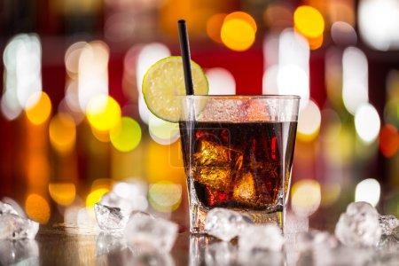 Photo pour Verre de boisson au cola sur comptoir de bar avec glaçons - image libre de droit