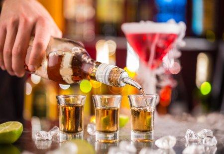 Photo pour Barman verser l'esprit dur dans des verres en détail - image libre de droit