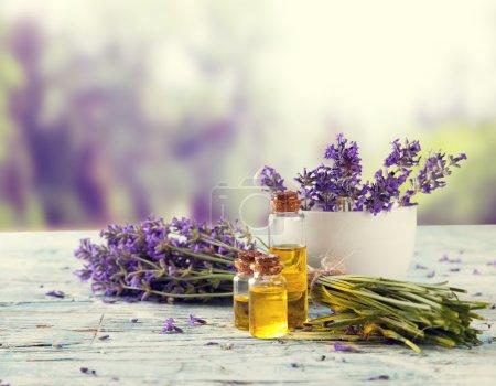 Photo pour Fleurs de lavande récoltées sur planches de bois, paysage flou sur fond - image libre de droit