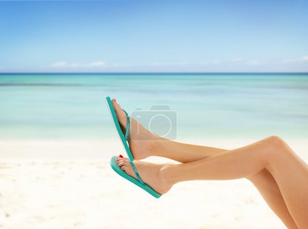 Slim female legs on sandy beach