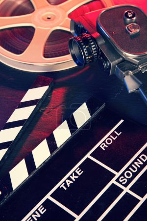 Cinema clapboard and reel on black stone