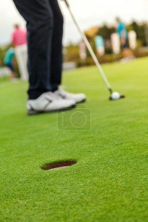 Photo pour Joueur de golf sur le putting-green. Frapper la balle dans un trou - image libre de droit