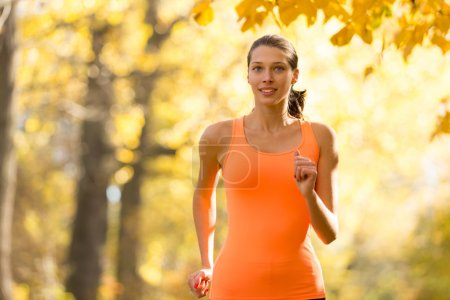 Female fitness model training outside and running.