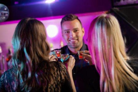 Photo pour Amis boire des coups ensemble à la boîte de nuit - image libre de droit